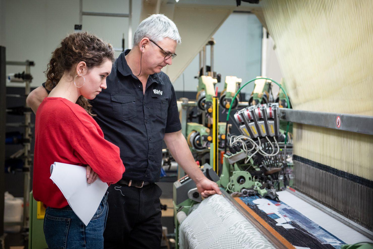twee mensen bij de weefmachine in het textiellab
