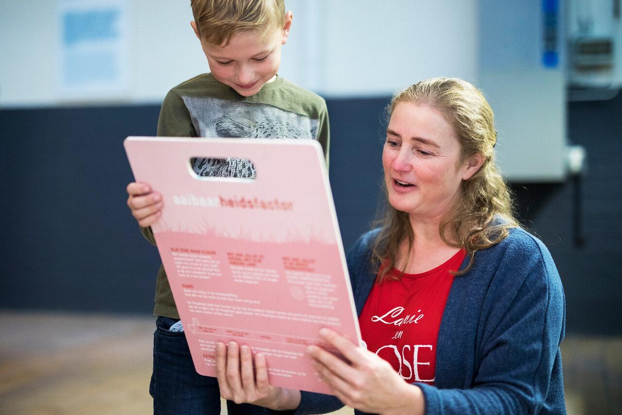 Moeder en kind houden een bord van het Speur & Ontdek spel vast