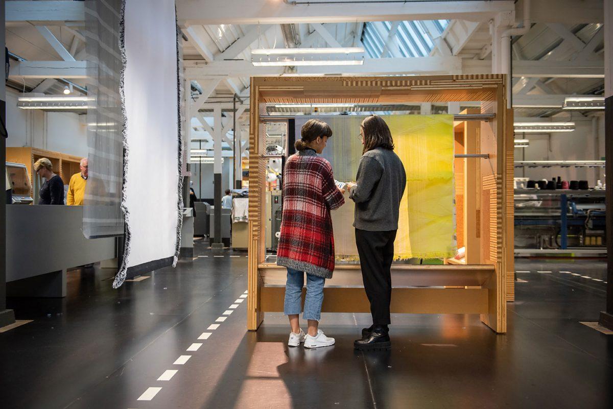 twee bezoekers in het textiellab, kijkend naar een kunstinstallatie