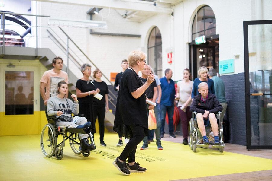 Bezoekers en rondleider in het TextielMuseum