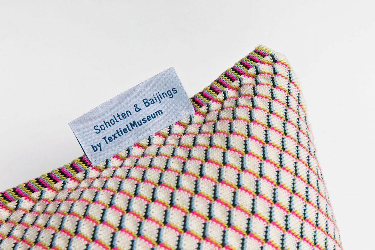 close up van het label van een gebreid Scholten & Baijings kussen voor het by.textielmuseum label