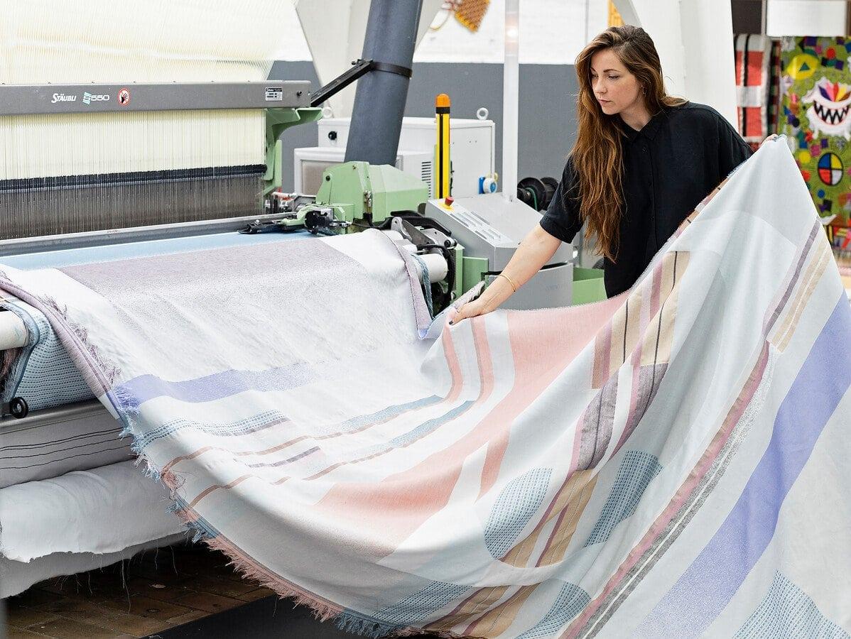 Mae Engelgeer houdt haar tafellaken vast vanuit de weefmachine in het TextielLab