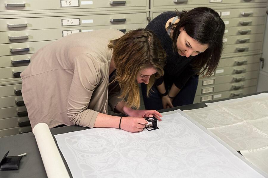 Lab medewerkers bij textiel stalen met vergrootglas