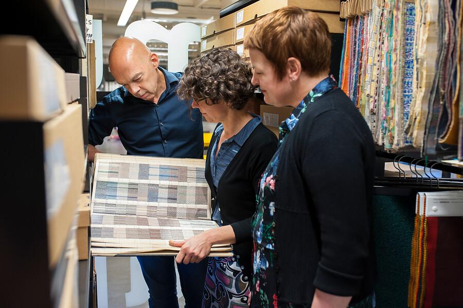 hoofd bibliotheek en twee bezoekers kijkend naar een boek met stalen
