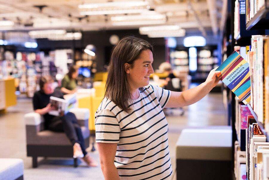 Bezoeker bekijkt boeken in bibliotheek van TextielMuseum