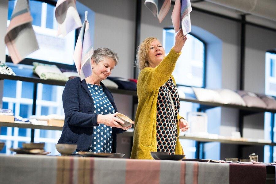 Bezoekers in de TextielShop kijkend naar theedoeken