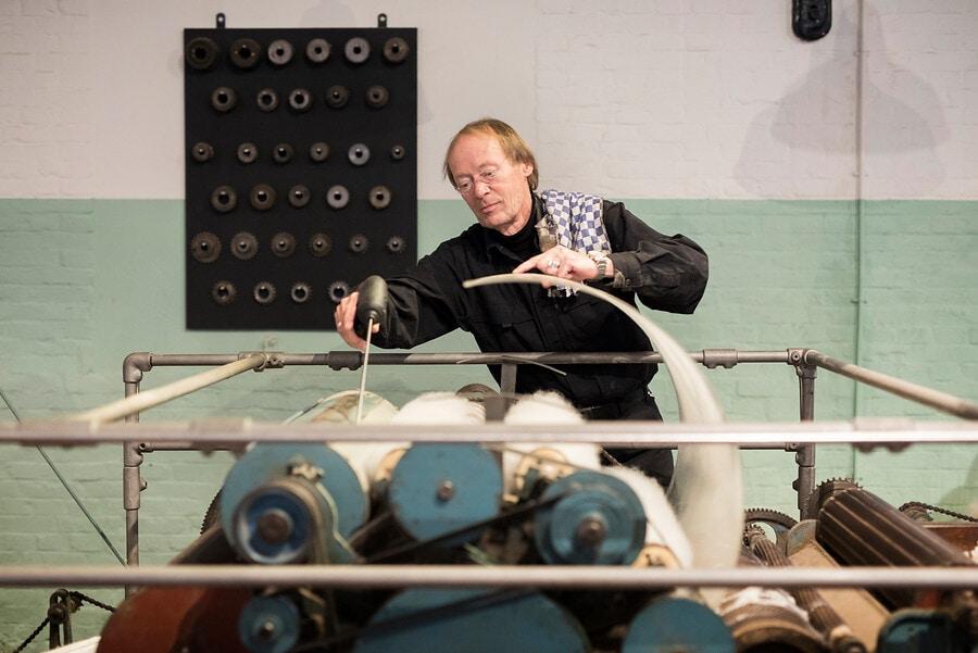 MedewMedewerker verzorgt machine wollendekenfabriek