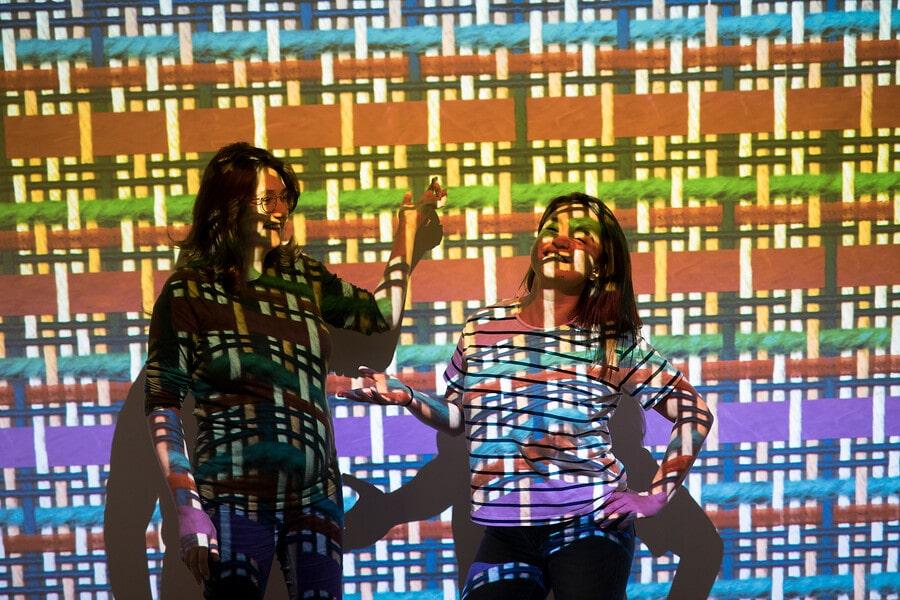 Bezoekers voor muur met eigen weef patroon afgebeeld door beamer