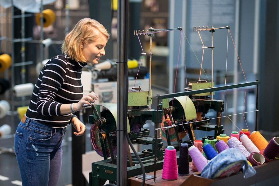 bezoeker in het TextielLab bij machine