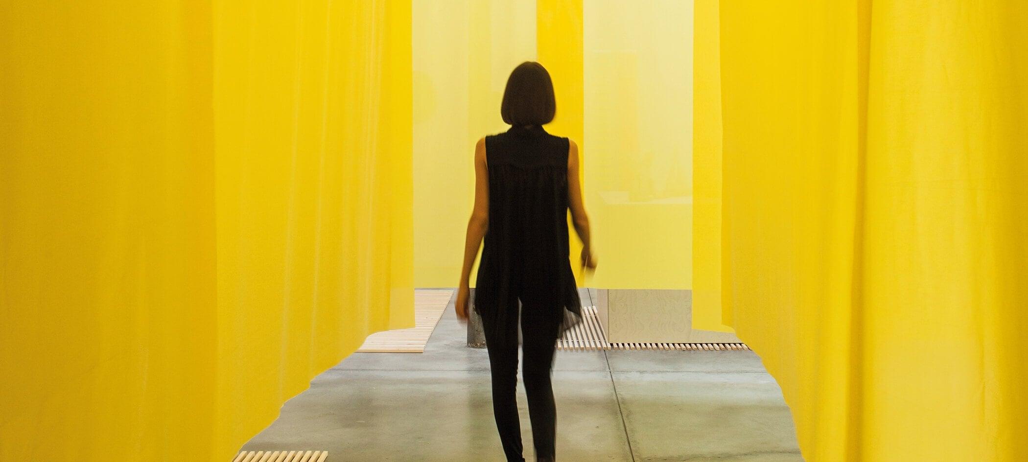 cover Toekomstvisie TextielMuseum - vrouw loopt tussen gelen doeken