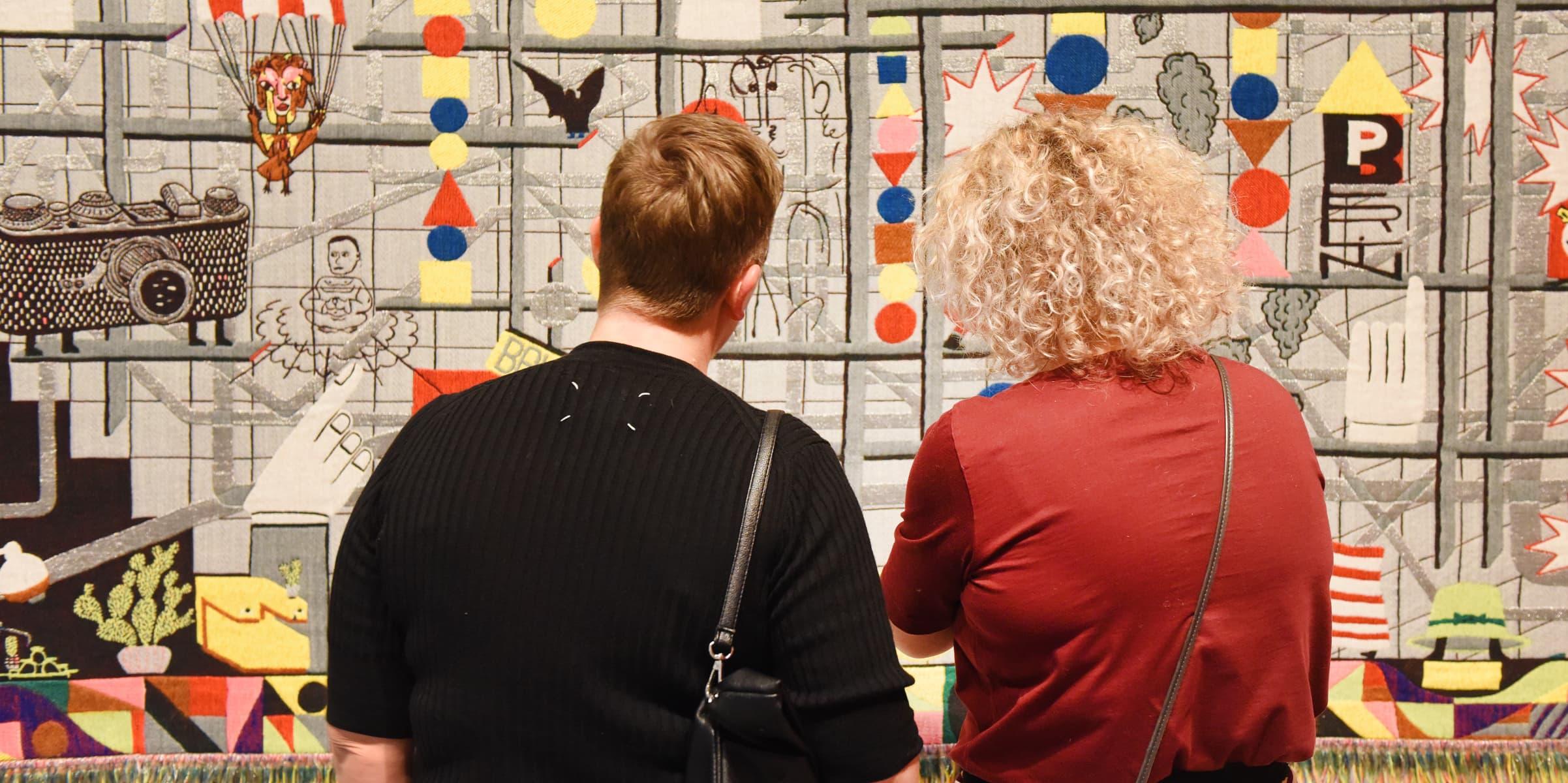 twee bezoekers bekijken kunst