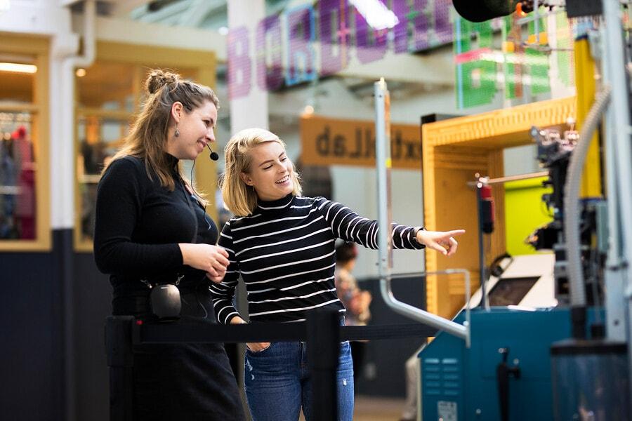 Rondleider en bezoeker kijken naar machine in het TextielLab
