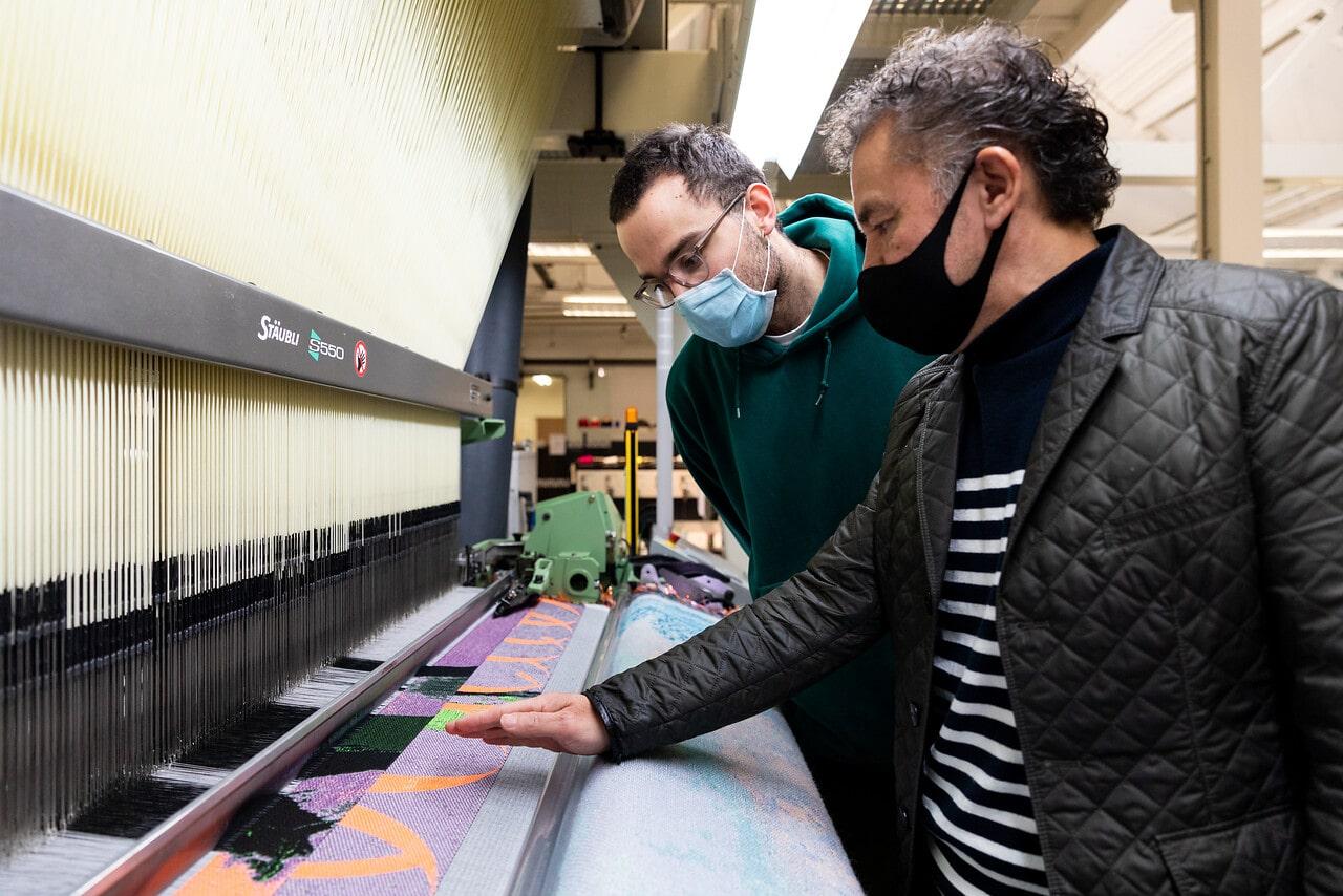 student en labmedewerker bij weefmachine
