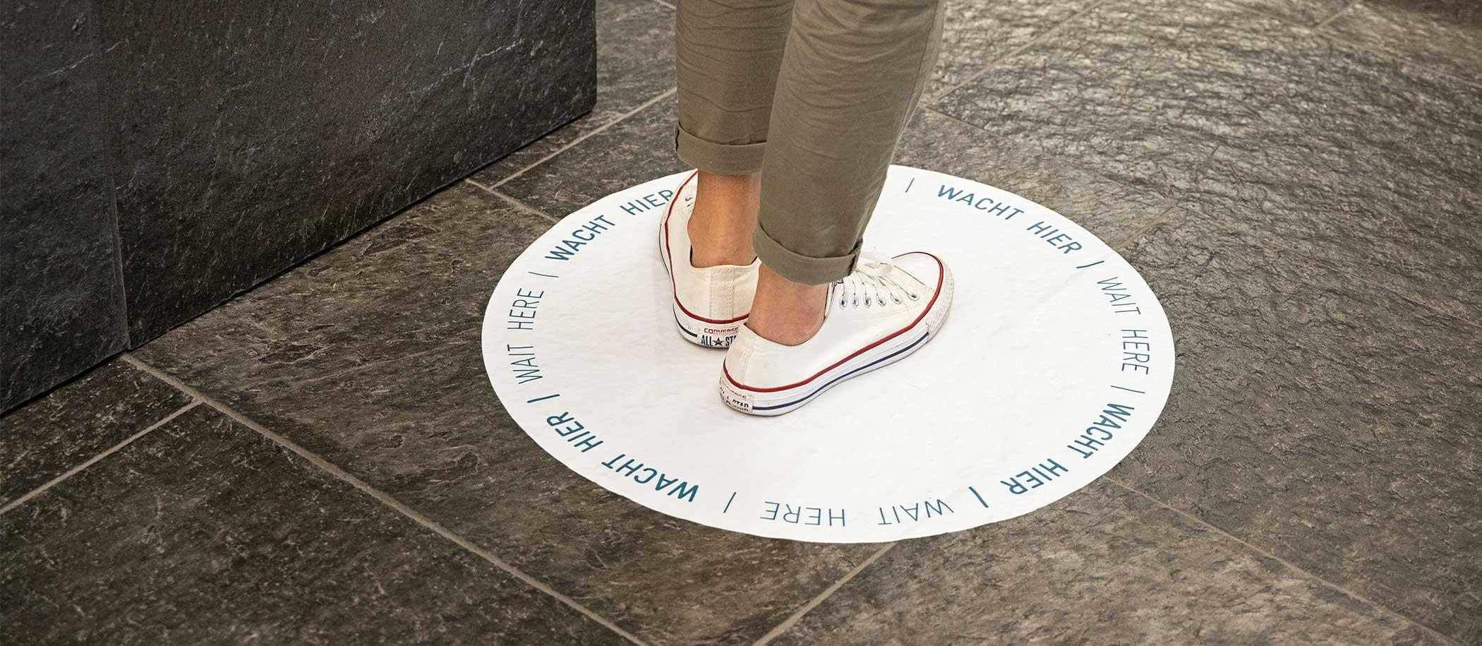 close up voeten op sticker op de vloer met de tekst 'wacht hier'