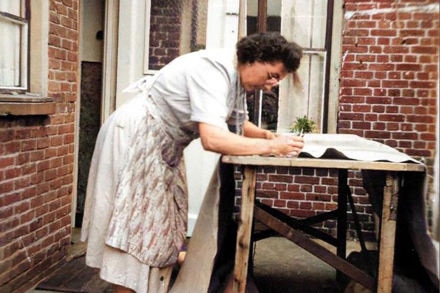 oude foto van vrouw die textiel aan het noppen is