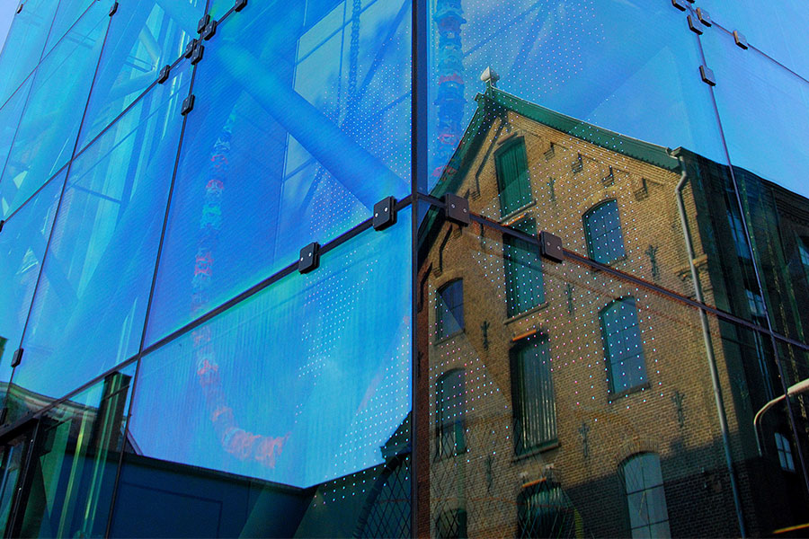 weerspiegeling villa in glazen entree gebouw TextielMuseum