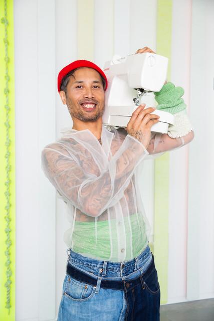Man met naaimachine in witte ruimte voor Long Live Fashion