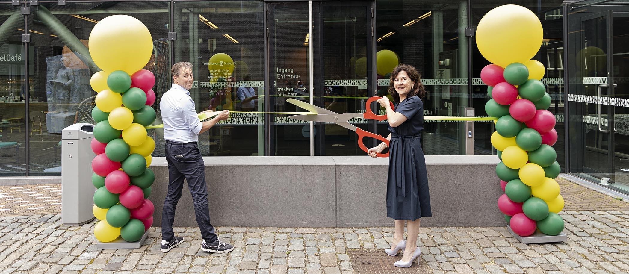 Marcelle Hendrickx met grote schaar knipt lint samen met directeur bij de entree van TextielMuseum