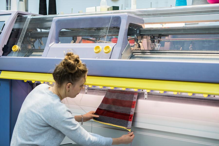 sjaal komt uit brei machine, labmedewerker staat er naast